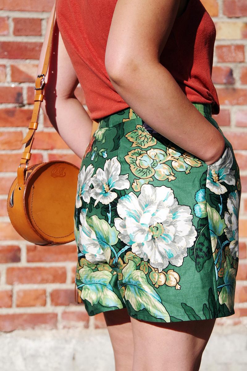 Korta sommarshorts sydda av återbrukat tyg. Vita, turkosa och roströda blommor och ljusgröna blad med inslag av senapsgult på mörkt blågrön botten. Sydda av Alicia Sivert som också står modell i ett rostrött linne och stråhatt mot en solig tegelvägg. Med på bild är även en rund läderväska handgjord av Jenny Lou Store. /// aliciasvert.se sy kläder klädsömnad gröna blommiga shorts med hög midja återbrukat tyg återbruk begagnat sömnad diy