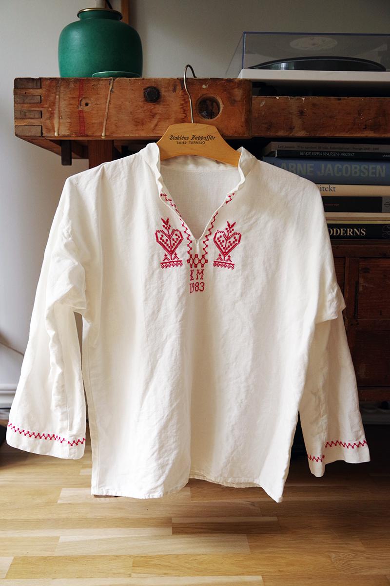 Vit linneskjorta med broderade detaljer i röda korsstygn runt hals och ärmslut. Bokstäverna KM och året 1983. Loppisfynd i Karin Larssons anda - www.aliciasivert.se
